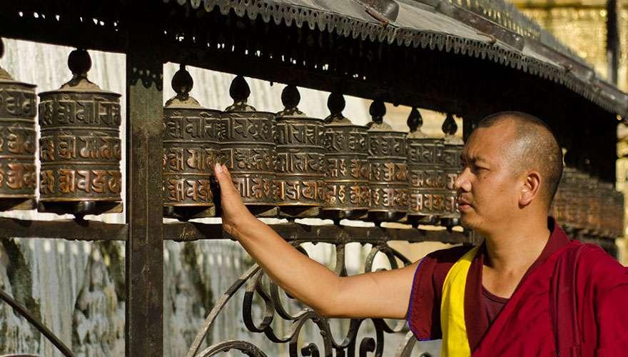 A Buddhist monk spins Prayer wheels  at Swayambhunath