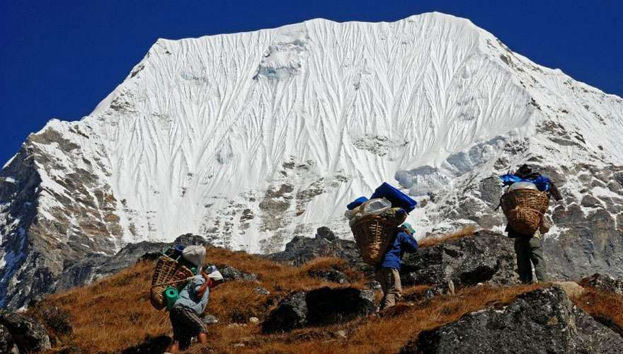 Porters walk beneath Chobutse Peak